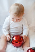 Beautiful baby boy playing with Christmas tree balls — Stock Photo
