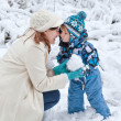 Royalty-Free Stock Photo: Young woman and her little son having fun with snow on winter da