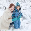 Young woman and her little son having fun with snow on winter da — Stock Photo #15618653