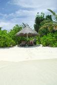 Silla de playa y paraguas en la idílica playa tropical de arena — Foto de Stock