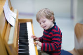 Two years old toddler boy playing piano — Стоковое фото