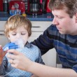 Little boy and his father making inhalation with nebuliser — Stock Photo #16343831