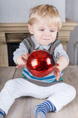 Little toddler playing with red Christmas tree ball — Stock Photo