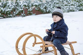 Lovely little boy on ancient sledge on winter day — Stock Photo