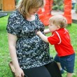 Stock Photo: Young pregnant womand little son in summer garden