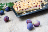Ripe plums and fresh baked cake on wooden table — Stock Photo
