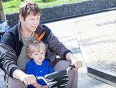Padre e hijo jugando juntos al aire libre en el coche de juguete — Foto de Stock