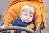 Ragazzo grazioso bambino all'aperto nel passeggino arancia — Foto Stock