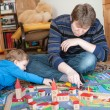 Father and little son playing with wooden railway toy — Stok fotoğraf