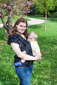 Young mother carrying baby son in rucksack in park — Stock Photo