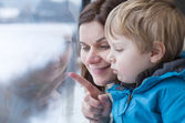 Mother and toddler son looking out train window outside — Stock Photo