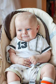 Beautiful baby boy with blue eyes 5 weeks old smiling and sitting in swing — Stock Photo