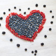 Heart made with red currant berries and blueberries - Stock Photo