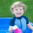 Little blond toddler boy playing with water in summer — Stock Photo