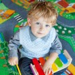 Little toddler boy playing with wooden music toy — Stock Photo