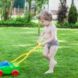 Little blond toddler boy playing with lawn mower — Stock fotografie