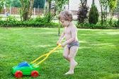 Niño rubio del niño jugando con cortadora de césped — Foto de Stock