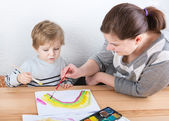 Mother and little boy of two years having fun painting — Stock Photo