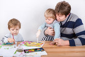 Father and two little boys siblings having fun painting — Stock Photo