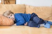Tired toddler boy laying on couch — Stock Photo