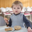 Little boy with eating bread and apple in kindergarten - Stock Photo