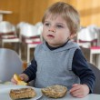 Stock Photo: Little boy with eating bread and apple in kindergarten