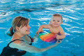 Little baby with blue eyes learning to swim — Stockfoto