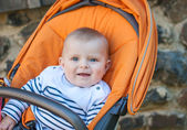 Lovely baby boy outdoor in orange stroller — Stock Photo