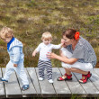 Stock Photo: Young mother and two little boys in summer nature park