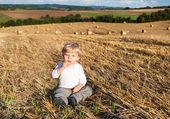 Little boy eating German sausage on goden hay field — Stock Photo
