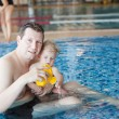 Stock Photo: Father and baby boy swimming in swimming pool