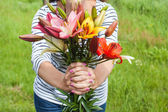 Beautiful lily bouquet holding by a woman — Stock Photo