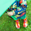 Little boy in rain clothes and boots hiding under green umbrella — Stock Photo #22758390