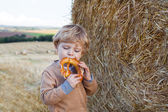 Cute toddler eating German pretzel on goden hay field — Stock Photo
