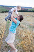 Young mother and her little son having fun in straw field — Stock Photo