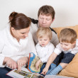 Stock Photo: Happy family of four watching old photos at home.