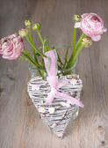 Ranunculus flowers in a vase with pink heart — Stock Photo