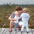 Young mother and two little boys in summer nature park — Stock Photo
