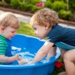 Stock Photo: Two sibling boys having fun with water in summer