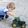 Little toddler boy playing with sand and toy — Stock Photo #23826343