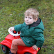 Little todder boy playing with big toy car — Stock Photo #24000765