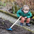 Little boy in spring with garden hoe — Stock Photo #24000803