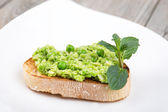 Delicious crostini with puree of raw beans and peas — Stock Photo