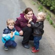 Young woman and two little boys eating ice cream - Stock Photo