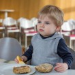 Little boy eating bread and apple in playschool — Stock Photo #24419473