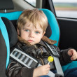 Toddler in safety car seat eating candy — Stock Photo