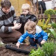 Stock Photo: Two little boys and father planting seeds