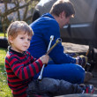 Little boy and his father changing wheel on car — Stock Photo #24967095