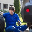 Young man changing wheel on car  — Stock Photo