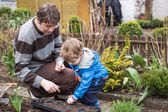 Little boy and his father planting seeds in vegetable garden — Stock Photo